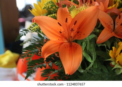 Orange lily in a flower bouquet with also Carthamus and other.