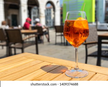 Orange liqueur. Aperol. A glass with orange liqueur on wooden table in luxury restaurant. Aperitif. Bright orange italian aperitif. Beverage glass with ice cubes and orange slices. Relax Cafe Alcohol.
