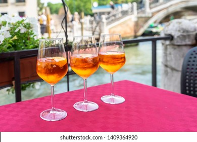Orange liqueur. Three glasses with orange liqueur on bright tablecloth in luxury restaurant. Bright orange italian aperitif. Three drinks glasses with ice cubes and orange slices. Relax Cafe Alcohol.