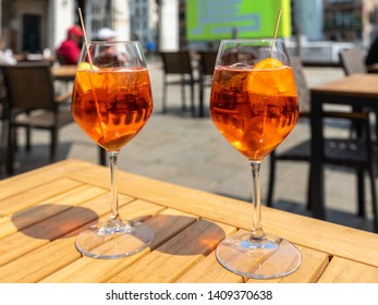 Orange liqueur. Two glasses with orange liqueur on wooden table in luxury restaurant. Bright orange italian aperitif. Two beverages glasses with ice cubes and orange slices. Relax Cafe Alcohol.