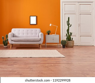 Orange living room and orange wall background light grey sofa and avangard white door. Modern home decoration brown parquet and carpet design.
