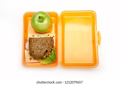 orange lunch box with bread and apple on white background, isolated
