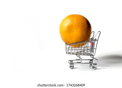 An orange is lying in a toy grocery cart on a white background