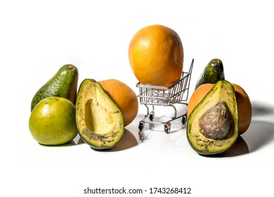 An orange is lying in a toy grocery cart next to fruit on a white background