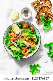 Orange marinated prawns, avocado, garden herbs salad - delicious healthy snack, appetizers, tapas on a light background, top view. Flat lay