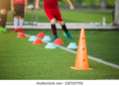 Orange marker cones on green artificial turf with blurry kid soccer player jogging between marker cones for training. Soccer training equipment.  Football or soccer academy.