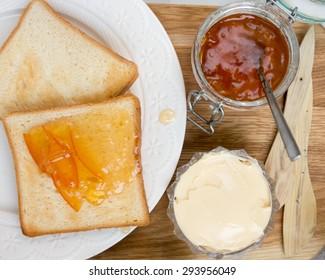 Orange marmalade toasts on a wooden set