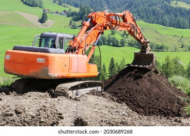 Orange mechanical digger working on a field