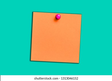 Orange memo card with pink pin. Note paper empty copy message space isolated on blue with shadow.