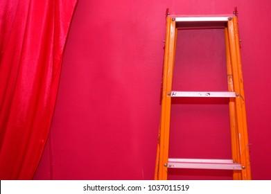 orange metal ladder on red wall