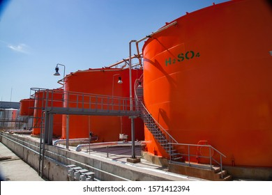 Orange metal storage tanks with acid and its formula on sulfuric (sulphuric) acid plant warehouse. Clear blue sky
