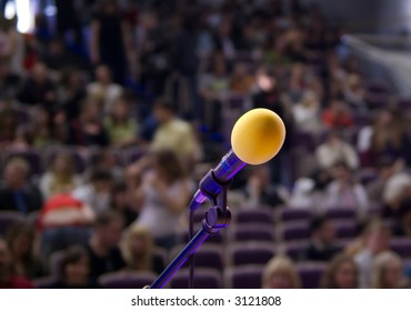 orange microphone on the stage and audience