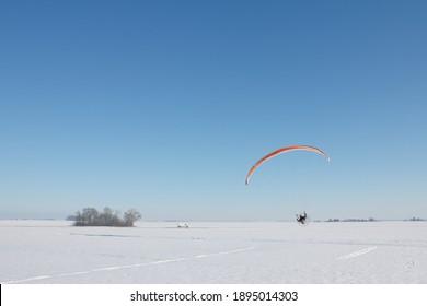 Parapente à moteur orange volant dans un champ de neige en hiver avec horizon et ciel bleu