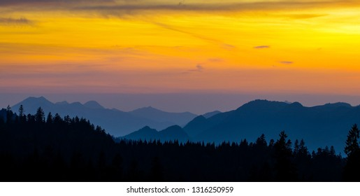 Orange mountain silhouette background. Trees and mountain tops in golden hour sunset