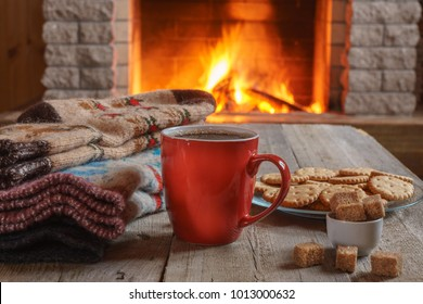Orange mug for tea or coffee with cookies ans sugar, wool things against cozy fireplace background; winter vacations,horizontal.