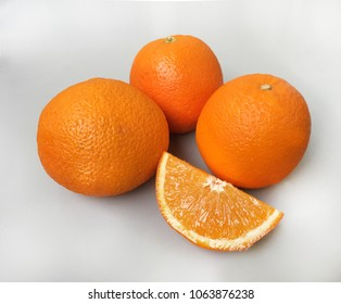 orange navel 3 pieces on grey background. one big, one medium and one small.