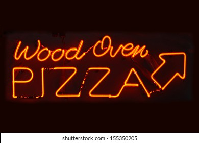 An orange neon sign reading Wood Oven Pizza