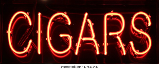 An orange neon sign that reads Cigars