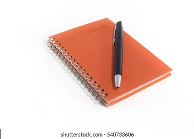 Orange notebook with black pen on white background.