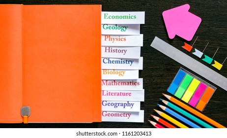 Orange notebook with the name of school subjects and with school supplies. Back to school. Education concept. Top view. Multi-colored letters and numbers