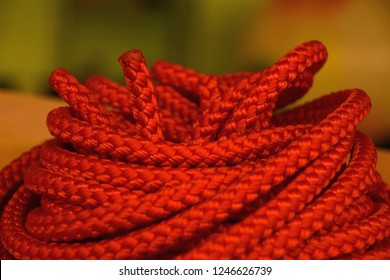 orange nylon rope roll in front of blurred background, coiled orange industrial rope made of nylon or synthetic