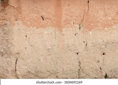 Orange old plaster wall with crack. The wall is faded and damaged.