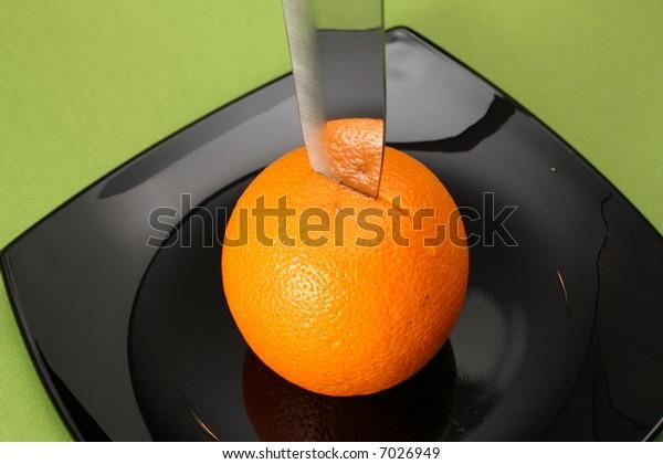 Orange on black plate with knife.