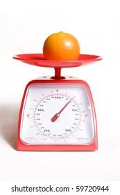 orange on kitchen food scale on white background
