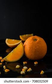 orange on slate stone with dark background. water drop on orange. fresh fruit  concept