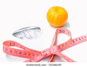 orange on Weight scales tied pink measuring tape. Selective focus,Conception about health care
