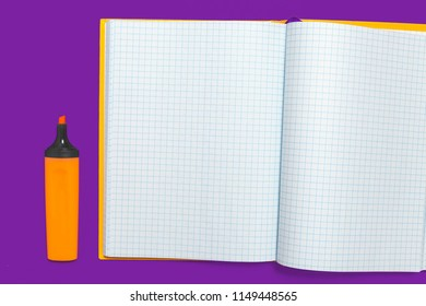 orange opened marker lying near the white workbook. concept of office and educational chancery. free copyspace