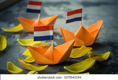 Orange origami boats with Dutch flag, with tulip petals . Celebration of Dutch traditional king's day - Koningsdag. 27 april.Handcraft hobby.