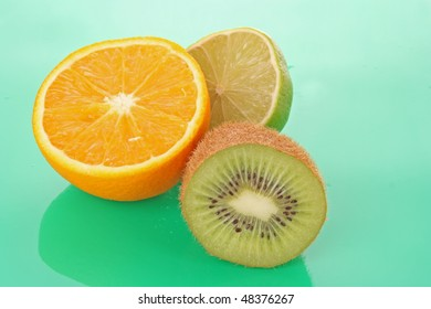 Orange and other fruits on green