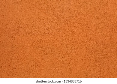 Orange painted stucco wall on Burano Island in the Venetian Lagoon near Venice, Italy. Background texture.