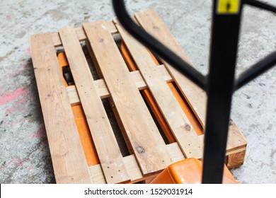Orange pallet truck, pallet truck with empty pallet, pallet jack transport warehouse storage