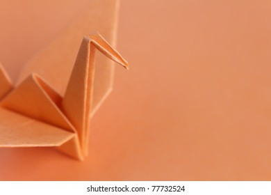 An orange paper bird on an orange background, shallow depth of field