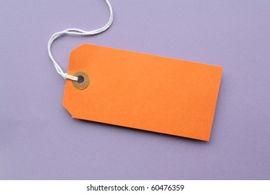 Orange paper luggage tag with copy space on a purple background