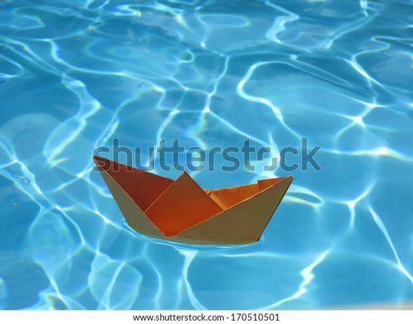 a orange paper ship on clear blue water