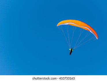 orange paraglider against the blue winter sky