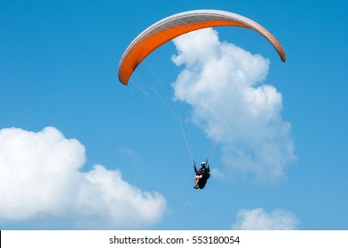Orange paraglider is flying in the blue sky against the background of clouds. Paragliding in the sky on a sunny day.