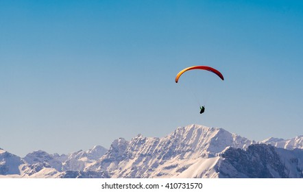 orange paraglider flying through the austrian alps