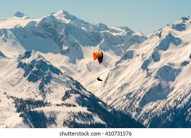 orange paraglider flying through the austrian alps