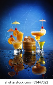 Orange party drinks on blue. Passion Daiquiri; Mango Margarita; Screwdriver and Shooters