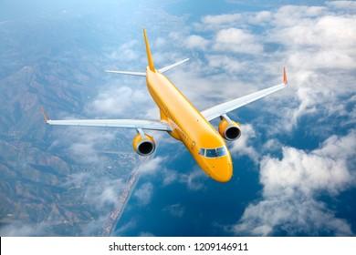 Orange passenger plane in flight. The orange aircraft flies high above the clouds.