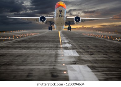 Orange passenger plane in flight. Aircraft takes off from the airport runway during the sunset. Front view.