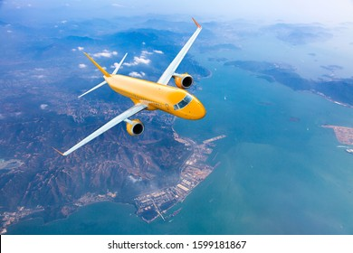 Orange passenger plane in flight. Aircraft flies high over the city and the sea coast. Aircraft top view.