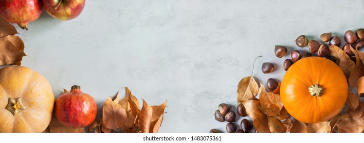 Orange and peachy pumpkins ripe organic red glossy apples pomegranates chestnuts dry yellow autumn leaves on gray marble stone background. Thanksgiving fall harvest abundance. Long banner copy space