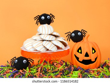 Orange pedestal with pumpkin muffin top cake cookies frosted, orange, black and green shredded paper below jack-o-lantern and fuzzy google eye spiders, orange background. Halloween theme.