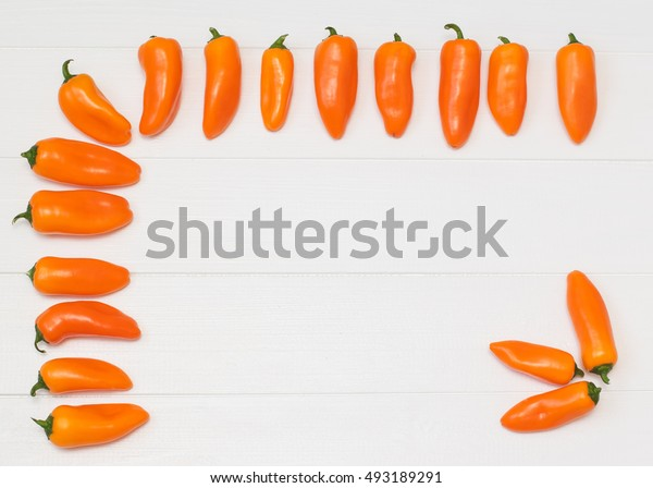 Orange pepper on a wooden table. Healthy food concept.