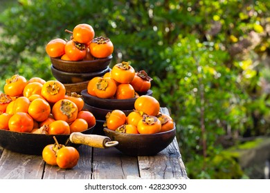 Orange persimmon kaki fruits in old clay plates on wooden old table in garden. Over nature background